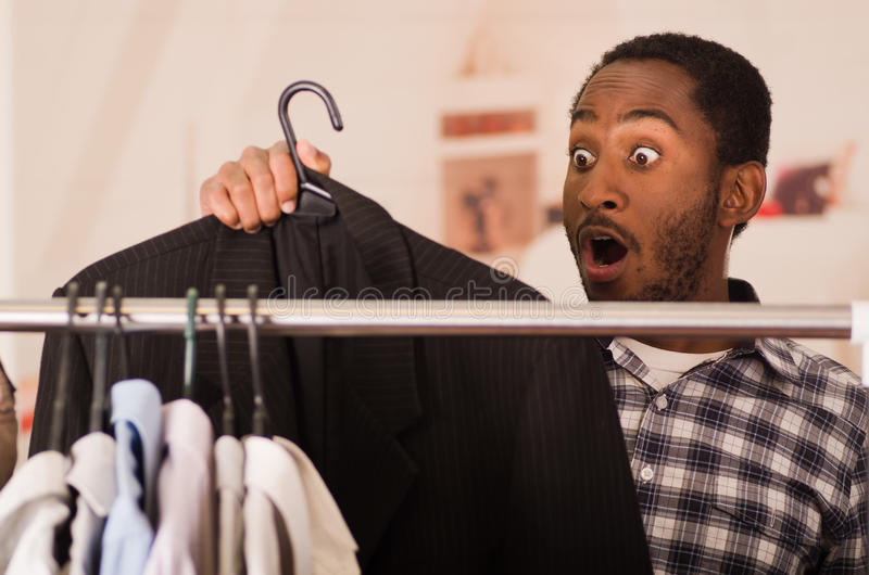 Hombre joven hermoso que coloca el guardarropa interior que pasa a través del estante de diversa ropa que cuelga, concepto de la  foto de archivo