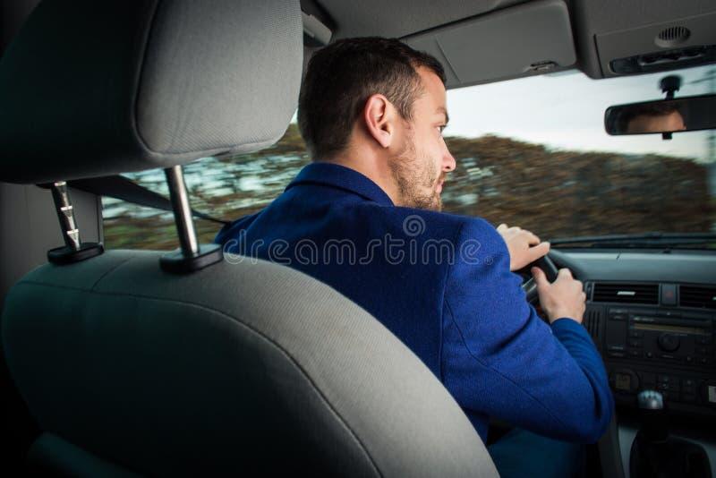 Hombre joven hermoso que conduce rápidamente su coche foto de archivo libre de regalías