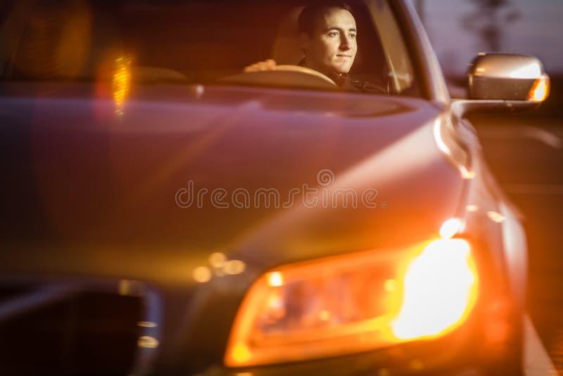 Hombre joven hermoso que conduce su coche en la noche imágenes de archivo libres de regalías