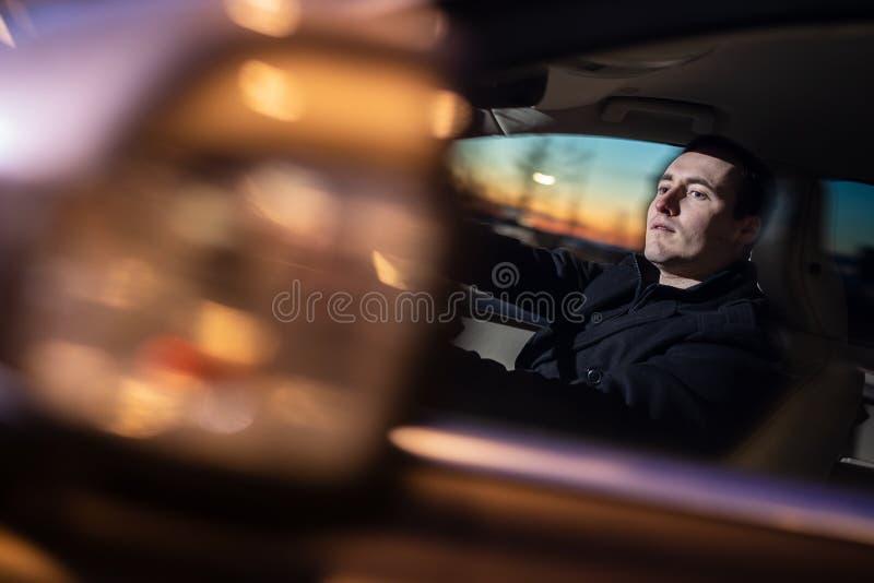 Hombre joven hermoso que conduce su coche en la noche fotografía de archivo