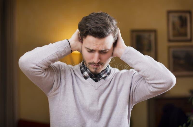 Hombre joven hermoso que cubre sus oídos, demasiado ruido imagenes de archivo