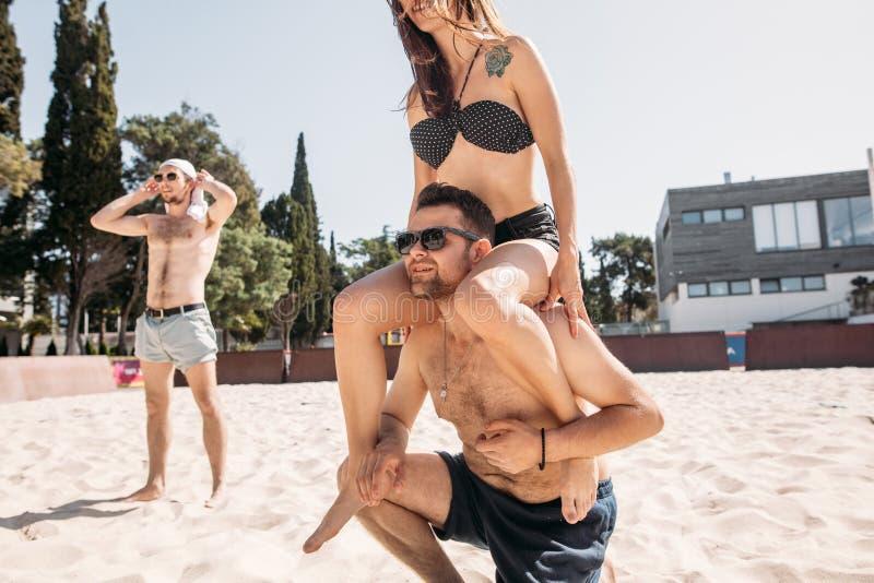 Hombre joven hermoso que da a cuestas paseo a su novia en la playa del verano imágenes de archivo libres de regalías