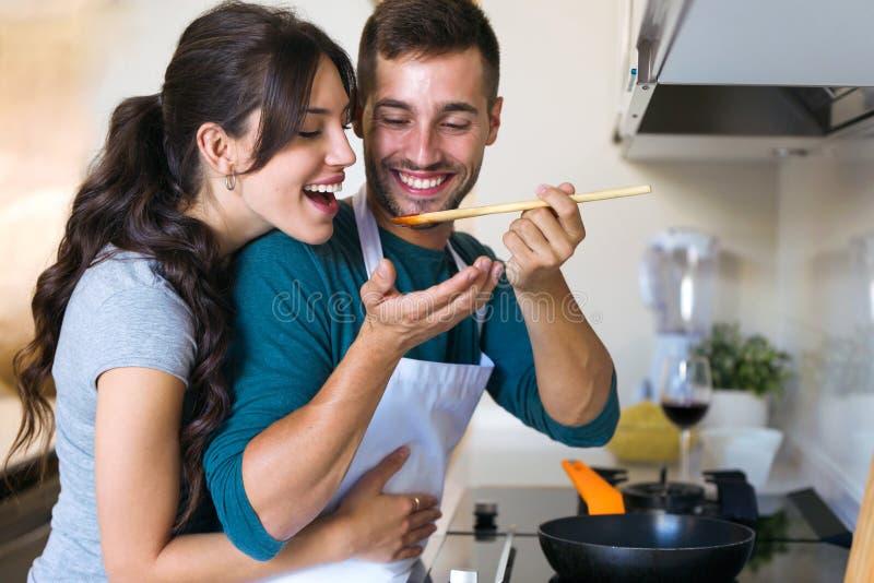 Hombre joven hermoso que da a su esposa para intentar la comida que él se está preparando en la cocina en casa foto de archivo libre de regalías