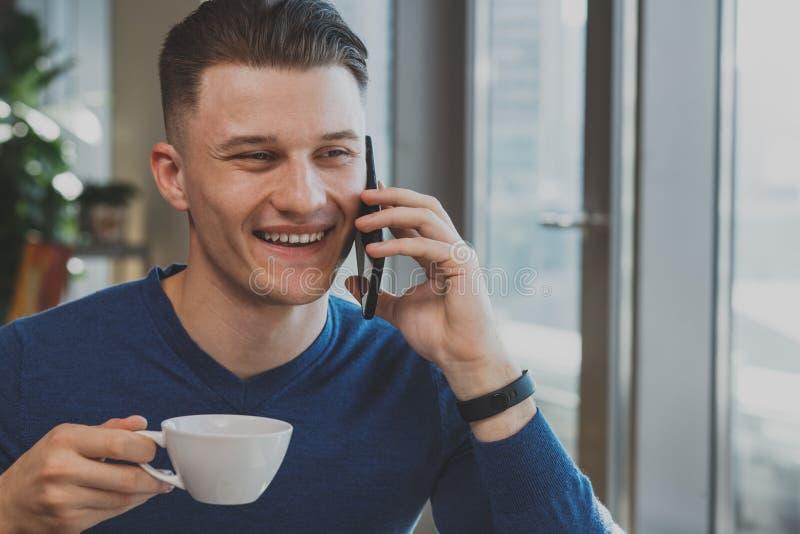 Hombre joven hermoso que desayuna en el café imagen de archivo