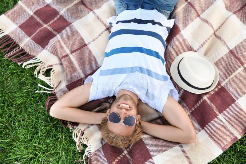 Hombre joven hermoso que descansa sobre la tela escocesa en parque foto de archivo