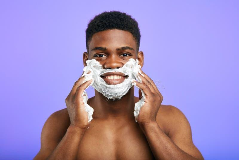Hombre joven hermoso que goza afeitando proceso fotos de archivo