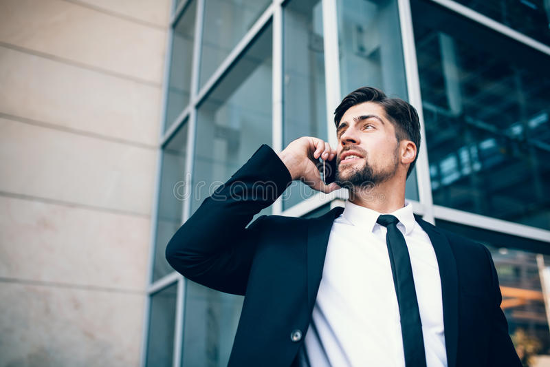 Hombre joven hermoso que habla en el teléfono móvil y que mira lejos fotografía de archivo libre de regalías