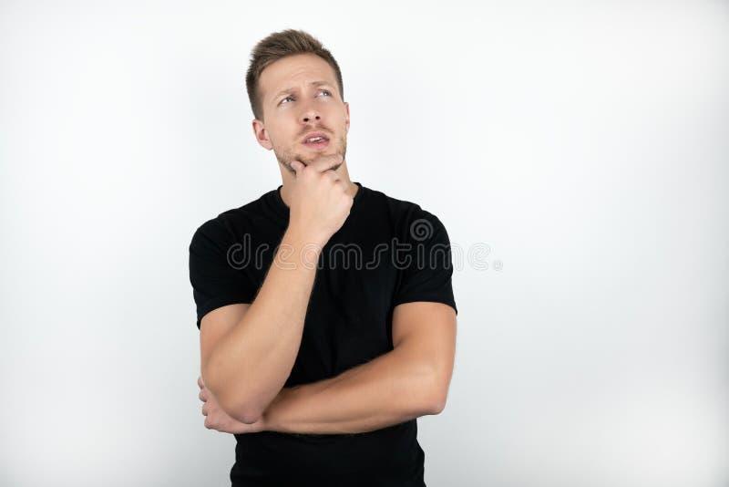 Hombre joven hermoso que lleva la camiseta negra que toca su cara con un fondo blanco aislado pensativo de las miradas de la mano fotos de archivo