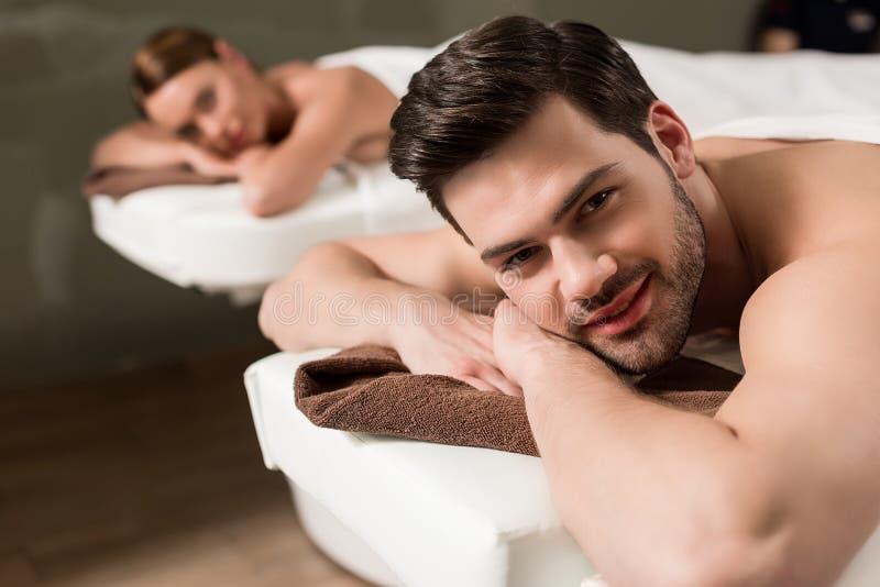 hombre joven hermoso que mira la cámara mientras que teniendo masaje en balneario imagen de archivo