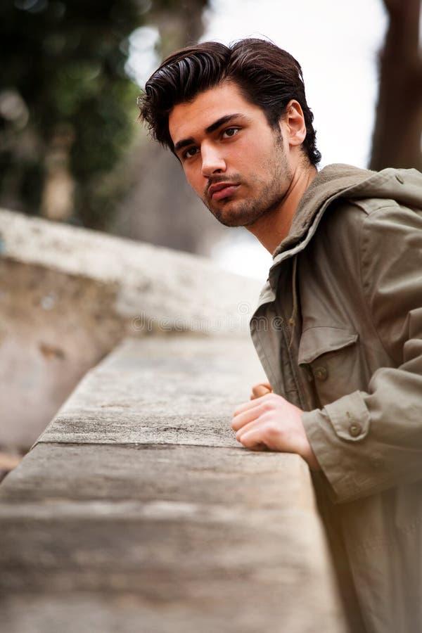 Hombre joven hermoso que mira que se inclina contra una pared imagenes de archivo