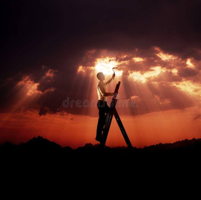 Hombre joven hermoso que pinta un cielo - concepto del negocio foto de archivo libre de regalías