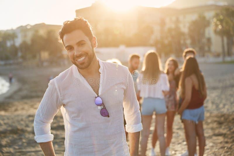 Hombre joven hermoso que se coloca en la playa con la sonrisa de los amigos foto de archivo