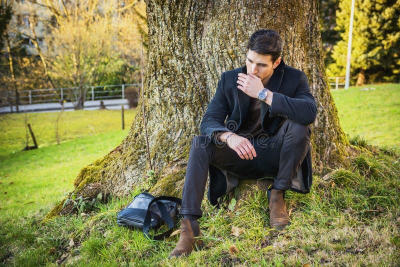 Hombre joven hermoso que se inclina contra árbol fotografía de archivo libre de regalías