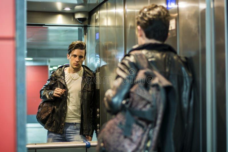 Hombre joven hermoso que se inclina contra el espejo en elevador o la elevación imagenes de archivo