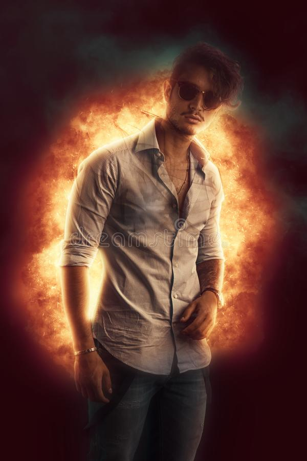 Hombre joven hermoso que se opone a la explosión de la llama fotos de archivo