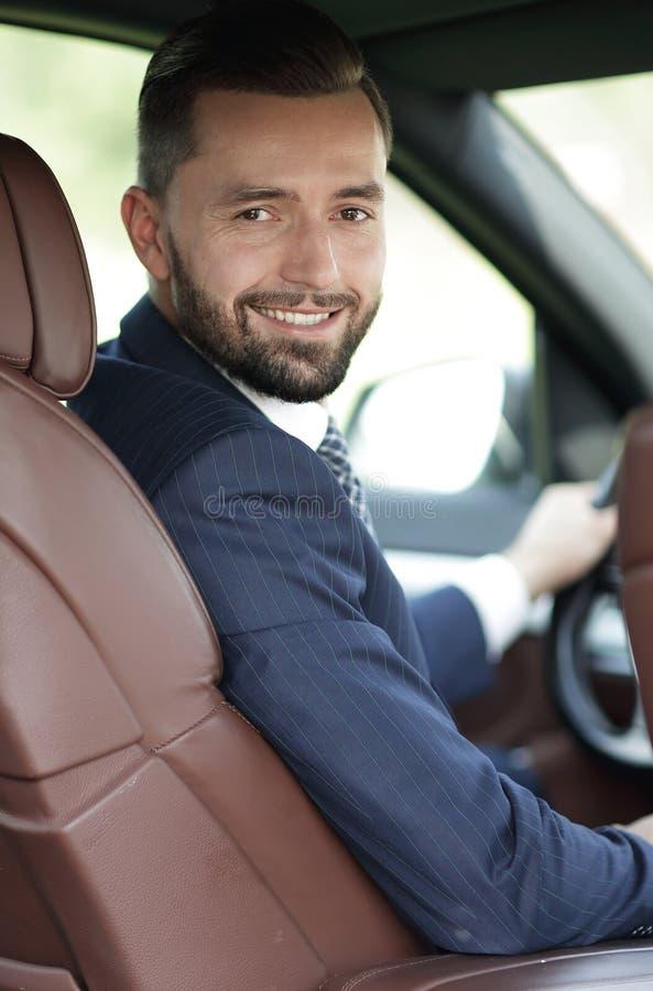 Hombre joven hermoso que se sienta en el asiento delantero de un coche que mira la cámara foto de archivo