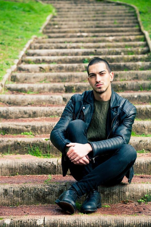 Hombre joven hermoso que se sienta en pasos al aire libre fotos de archivo libres de regalías