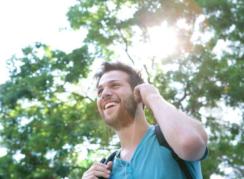 Hombre joven hermoso que sonríe con los auriculares al aire libre foto de archivo