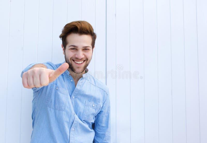 Hombre joven hermoso que sonríe con los pulgares para arriba fotos de archivo