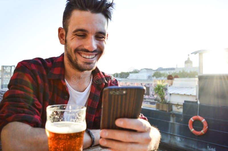 Hombre joven hermoso que sonríe mirando el teléfono y bebiendo una cerveza en una barra afuera imagen de archivo