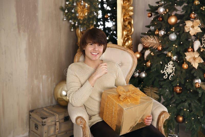 Hombre joven hermoso que sostiene la caja de regalo que se sienta en la butaca en beige fotos de archivo