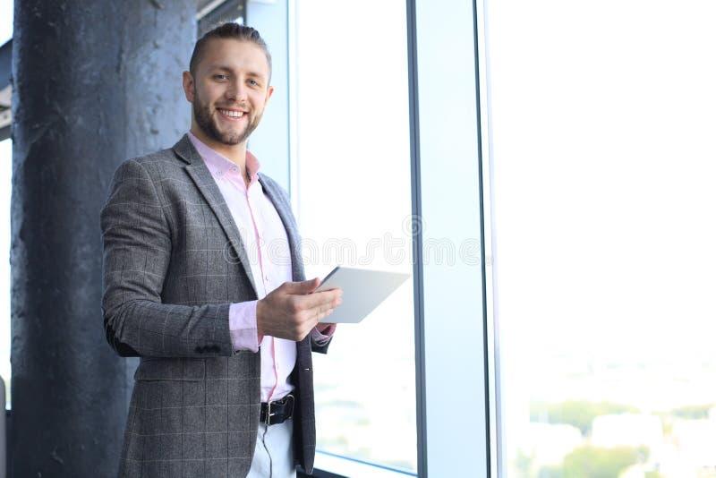 Hombre joven hermoso que sostiene la tableta digital y que mira la c?mara con sonrisa mientras que se coloca en la oficina foto de archivo
