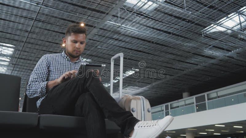 Hombre joven hermoso que sostiene Tablet PC y que trabaja en el aeropuerto, tecnología, concepto que viaja fotos de archivo libres de regalías