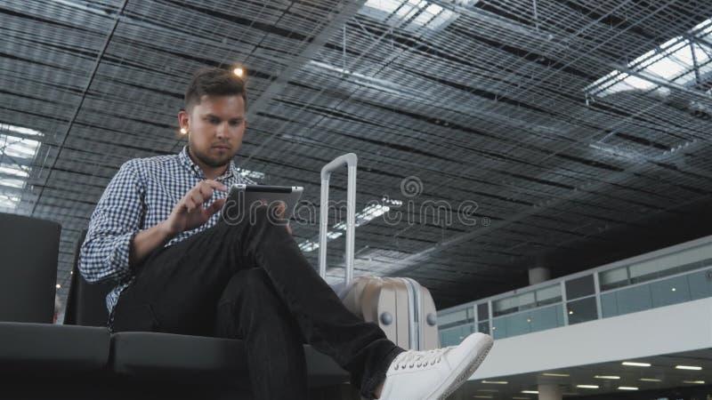 Hombre joven hermoso que sostiene Tablet PC y que trabaja en el aeropuerto, tecnología, concepto que viaja fotos de archivo