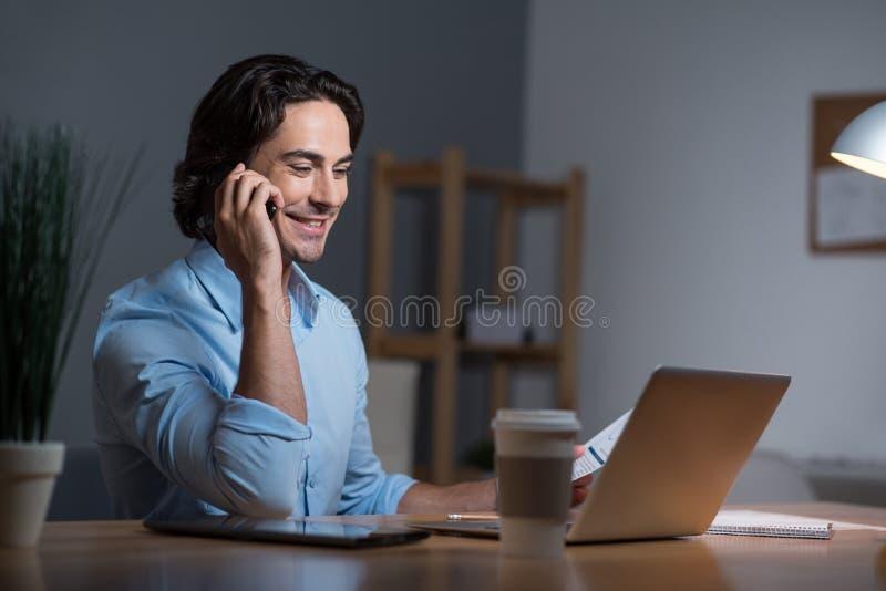 Hombre joven hermoso que tiene conversación sobre el teléfono móvil fotografía de archivo