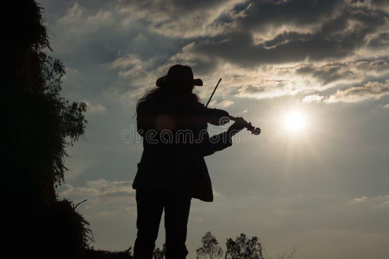 Hombre joven hermoso que toca el violín muy feliz La paja encendido fotografía de archivo
