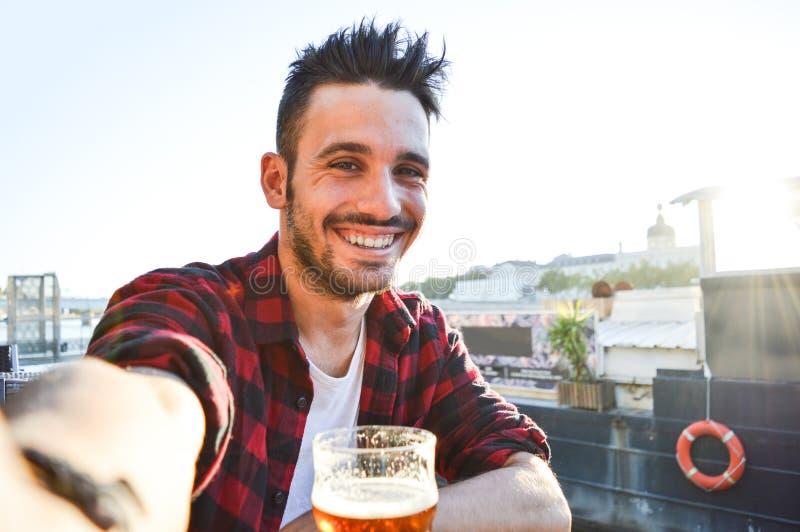 Hombre joven hermoso que toma un selfie que bebe una cerveza en la barra fotografía de archivo libre de regalías