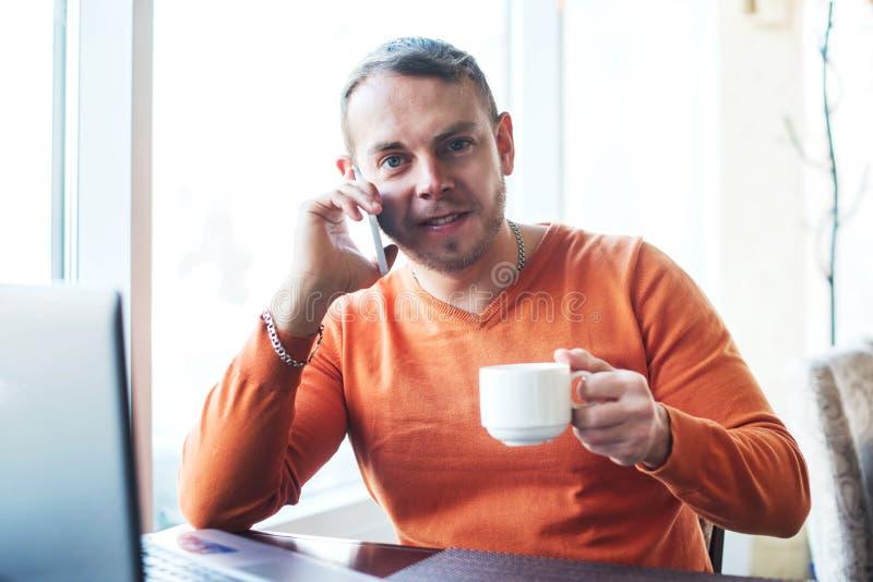 Hombre joven hermoso que trabaja con el cuaderno, hablando en el teléfono, sonrisa, mirando la cámara, mientras que goza del café foto de archivo