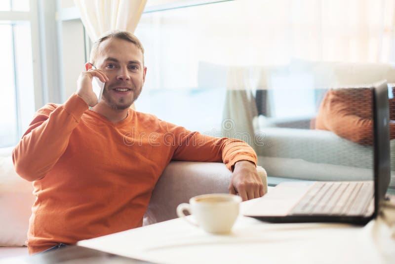 Hombre joven hermoso que trabaja con el cuaderno, hablando en el teléfono, sonrisa, mirando la cámara, mientras que goza del café imagen de archivo libre de regalías