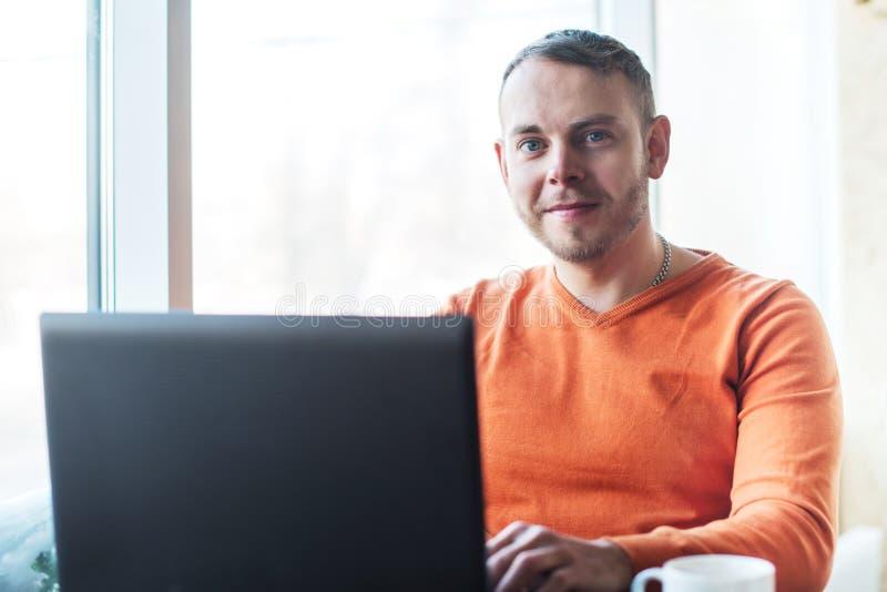 Hombre joven hermoso que trabaja en el cuaderno, sonrisa, mirando la cámara, mientras que goza del café en café foto de archivo
