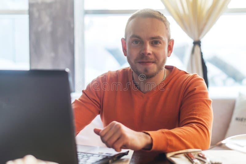 Hombre joven hermoso que trabaja en el cuaderno, sonrisa, mirando la cámara, mientras que goza del café en café imagen de archivo libre de regalías