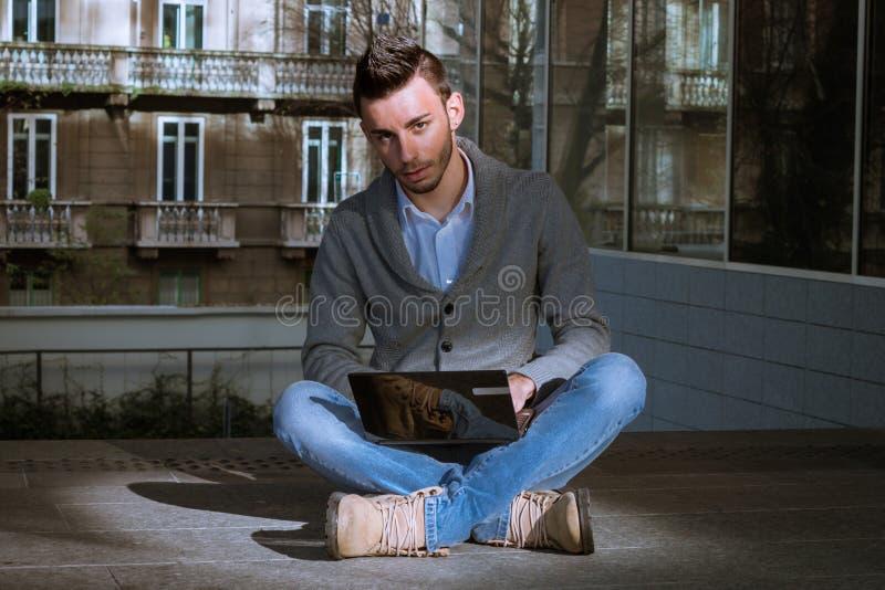 Hombre joven hermoso que trabaja en el ordenador fotografía de archivo libre de regalías