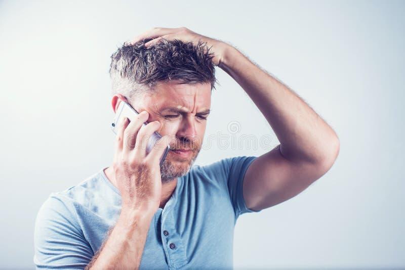Hombre joven hermoso que usa la sensación del teléfono móvil triste fotografía de archivo