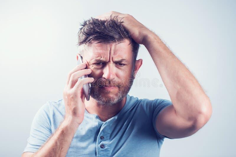 Hombre joven hermoso que usa la sensación del teléfono móvil triste imagen de archivo libre de regalías