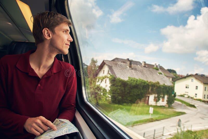 Hombre joven hermoso que usa un mapa en el tren viajero en el camino imágenes de archivo libres de regalías