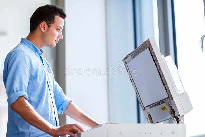Hombre joven hermoso que usa una máquina de la copia fotografía de archivo libre de regalías