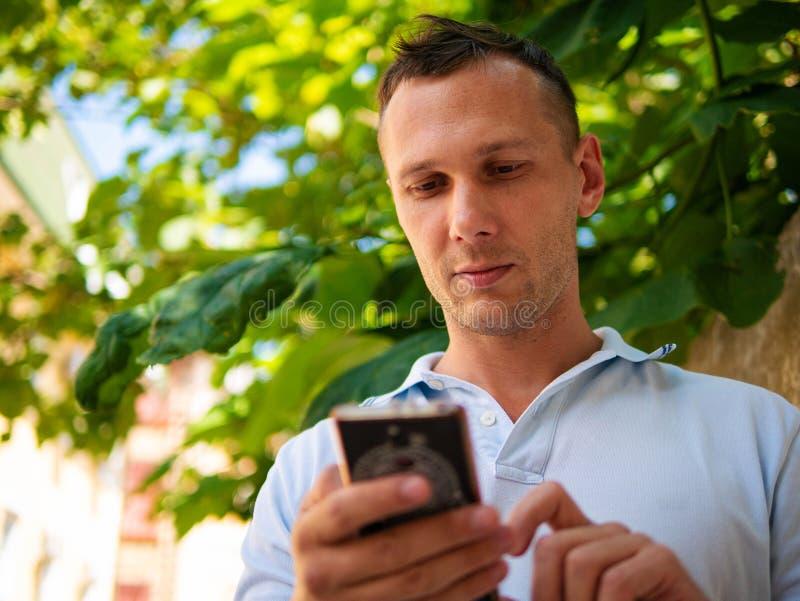 Hombre joven hermoso sobre el fondo blanco de la pared que charla por el teléfono móvil que mira a un lado imagen de archivo