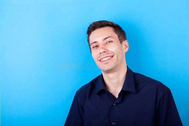 Hombre joven hermoso sonriente en fondo azul imagen de archivo