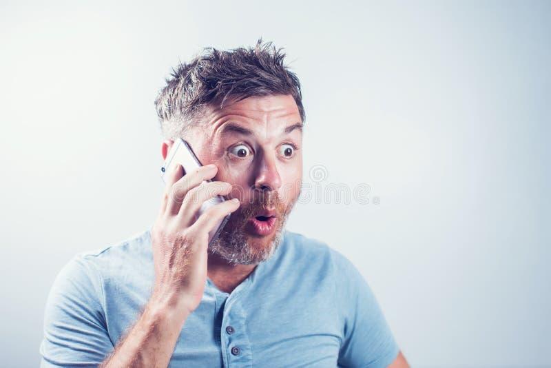 Hombre joven hermoso sorprendido usando el teléfono móvil imagen de archivo