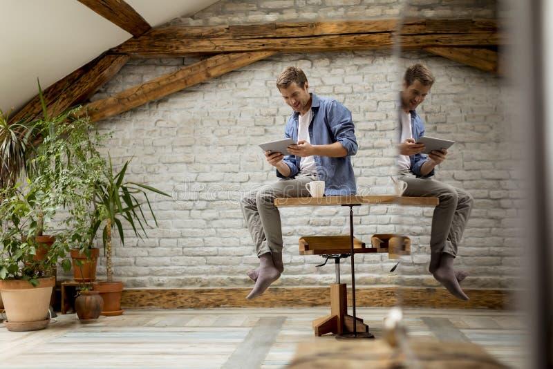 Hombre joven hermoso usando la tableta digital mientras que se sienta en el cuarto r?stico fotos de archivo libres de regalías