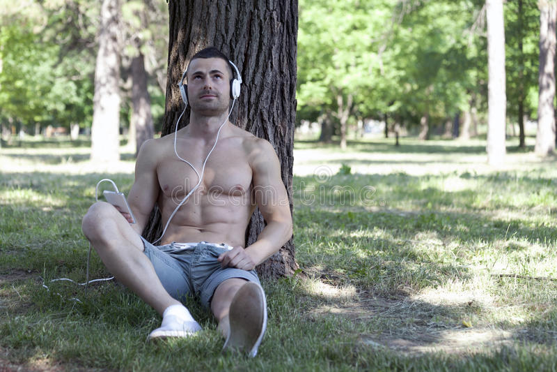 Hombre joven hermoso y atractivo que se relaja en naturaleza durante trai fotos de archivo