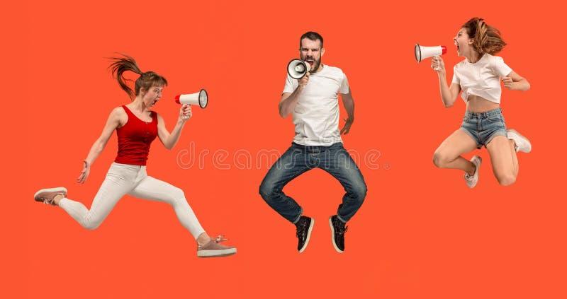 Hombre joven hermoso y mujer que saltan con el megáfono aislado sobre fondo rojo imagen de archivo