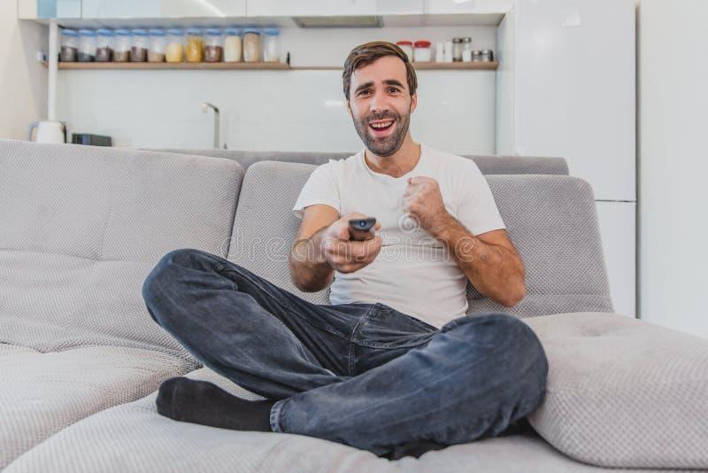 Hombre joven hilarante hermoso que sostiene un teledirigido Durante esto, la TV está mirando mientras que se sienta en el sofá en imagenes de archivo