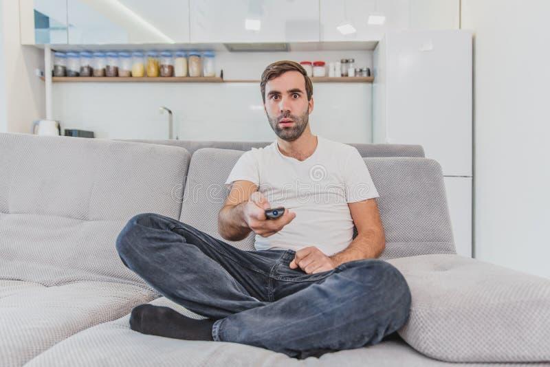 Hombre joven hilarante hermoso que sostiene un teledirigido Durante esto, la TV está mirando mientras que se sienta en el sofá en fotografía de archivo