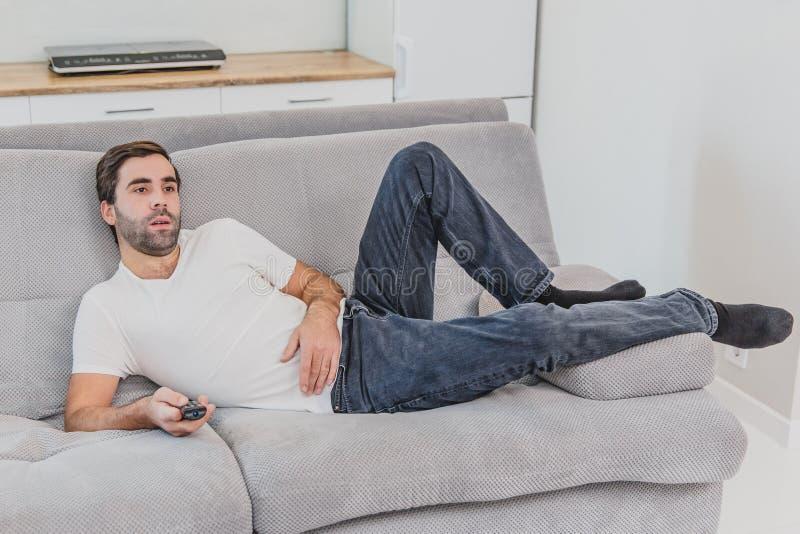 Hombre joven hilarante hermoso que sostiene un teledirigido Durante esto, la TV está mirando mientras que se sienta en el sofá en imagen de archivo libre de regalías
