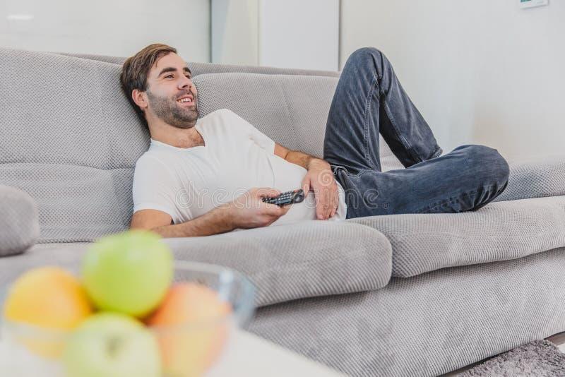 Hombre joven hilarante hermoso que sostiene un teledirigido Durante esto, la TV está mirando mientras que se sienta en el sofá en fotos de archivo